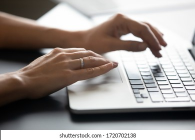 Close up female hands typing on laptop keyboard, woman blogger working online, writing financial report, blog or email, chatting with friends in social network, using computer apps