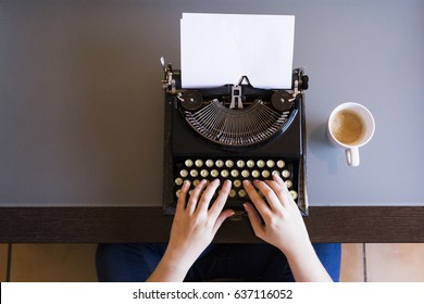 Close up of female hands typing on retro typewriter. Cup of coffee is at right side. Top view. Indoors