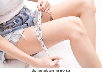 Close up of female hands using measuring tape measuring her legs size (healthy and weight loss or diet concept) isolated on white background