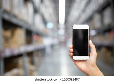 Close up of female hands using smart phone on blurred warehouse background. Using for Mock up template for display of your design,Banner for advertise of product.