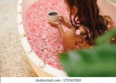 Close up female hands with white cup of herbal tea in stone bath tube with tropical flowers, organic skin care, luxury spa hotel, Bali Indonesia