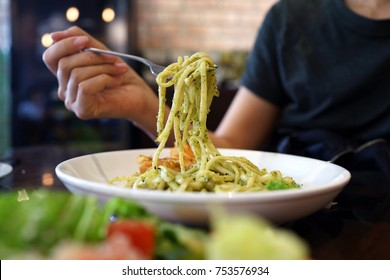 Close up of female having Spaghetti with pesto sauce for lunch