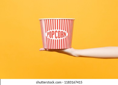 Close up female hold in hand classic clear empty striped xl bucket for popcorn isolated on trending yellow orange background. Cinematography production, takeaway food concept. Copy space advertising