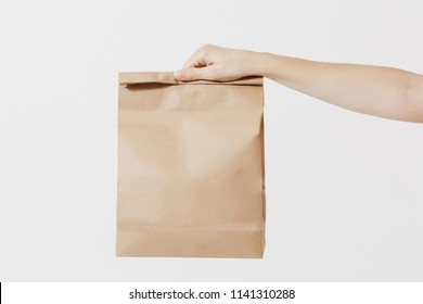 Close up female holds in hand brown clear empty blank craft paper bag for takeaway isolated on white background. Packaging template mock up. Delivery service concept. Copy space. Advertising area