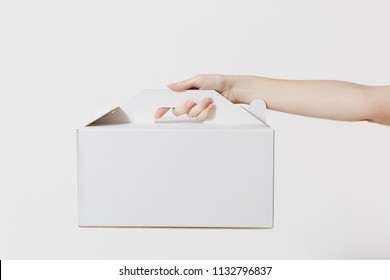 Close up female holds in hand cake dessert in unmarked clear empty blank cardboard box, food order isolated on white background. Delivery concept. Copy space Advertising area Receiving package mock up