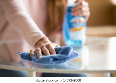 Close up of female housekeeper specialist hold blue duster cleaning glass table perform housekeeping job service, woman make daily house chores dust off using cloth with spray fluid detergent