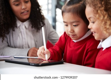 Close up of female infant school teacher sitting at a desk in a classroom helping two schoolgirls wearing school uniforms using a tablet computer and stylus, looking at screen and smiling