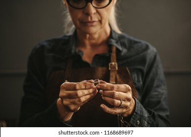 Close up of female jeweler hands examining the silver ring at workshop. Woman goldsmith inspecting jewelry.