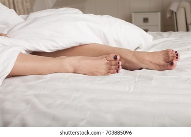 Close up of female legs on white in a bed.