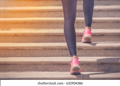 Close up of female legs with sneakers running up the stairs. Sport, fitness, jogging, workout and healthy lifestyle concepts.