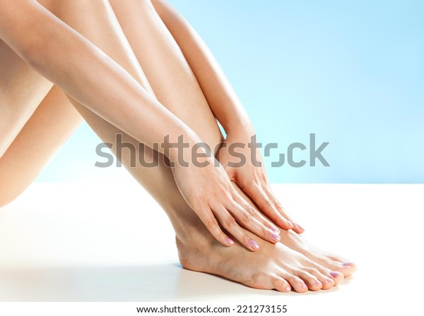 Close up of female legs. Woman applying moisturizer.