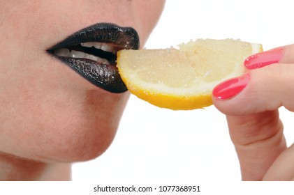 Close up of female lips with a slice of lemon sugar, black lipstick, white background