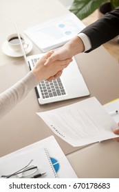 Close up of female and male shaking hands, businessman and businesswoman handshaking above office table with charts graphs after successful negotiations, partners concluding contract, top view