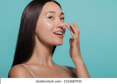 Close up of female model applying moisturizer cream to her nose. Woman applying moisturizer cream on her face against blue background.