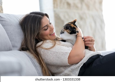 Close up of female owner holding her lovely black and white cat at home. Concept of love to animals, pets, care, tranquility.