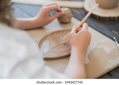 Close up of female potter holding stick and making ornament on earthenware. Clay master moulding clay product. Concept of ceramic art and hobby.