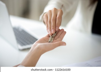 Close up of female real estate agent giving keys to woman buying first house, purchasing property or becoming homeowner, renting apartment or getting lease or mortgage investment. Ownership concept