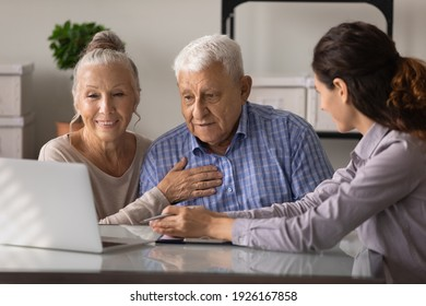 Close up female realtor manager real estate agent consulting mature couple about mortgage or rent, looking at laptop screen, senior family wife and husband listening to financial advisor broker