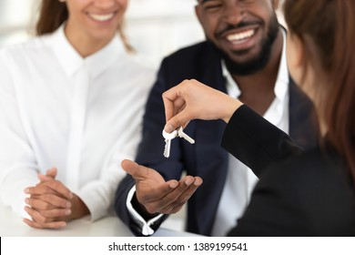 Close up of female realtor or real estate agent give house keys to excited multiethnic young married couple, woman broker greeting happy spouses become property owners, buying first home together