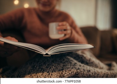 Close up of female sitting on sofa with open book and coffee. Woman reading book at home.
