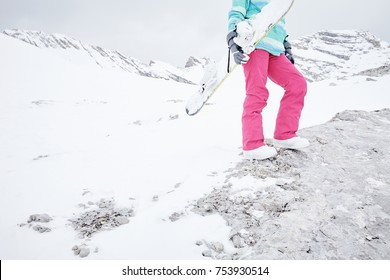 Close up of female snowboarder wearing white boots and pink pants standing on rock, holding snowboard in her hand and preparing for ride - snowboarding concept, copy space