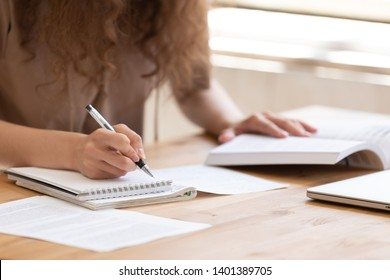 Close up of female student sit at table study using  handbook write in notebook doing research, motivated girl prepare for test or exam learning handwriting in workbook, making notes of important data