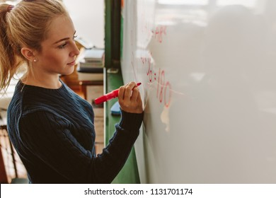 Close up of female student writing an equation on white board in classroom. Girl writing on board during maths class.