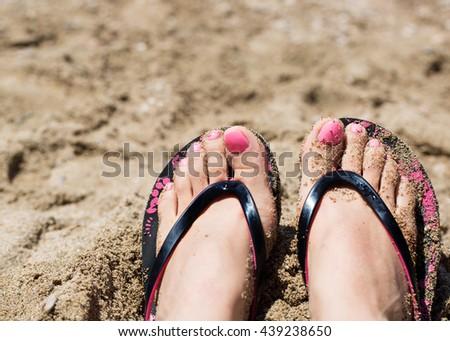 26f18d97b024f Close up of female sunbathing feet wearing flip flops near sea on sandy  beach
