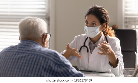 Close up female therapist wearing face mask consulting mature patient at meeting in hospital office, doctor talking, explaining, discussing medical checkup result or symptoms with older man