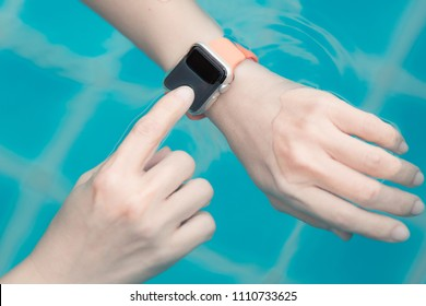 Close up of female using hands with the smart watch at the pool. Healthy lifestyle concept.