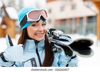 Close up of female wearing sports jacket and goggles who hands skis and thumbs up
