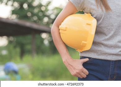 Close up of Female workers dressed in gray t-shirt and jeans holding a yellow helmet with copy space,Background for use as labor day