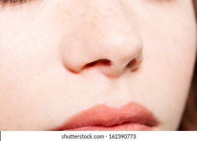 Close up of a female's face- nose and mouth.  Isolated on white.
