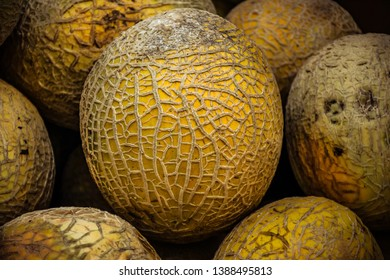 Close up of a field ripened cantaloupe at a local farmer's market with its webbing and natural flaws.