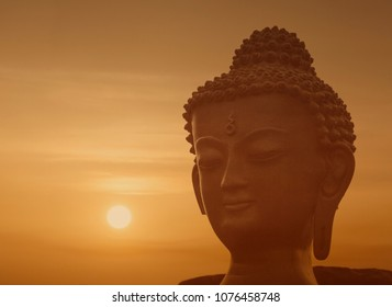 close up of figurine of Buddha against sunset