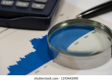 close up financial graph report with pen magnifier and calculator. This is financial report analysis is important for value investor concept.