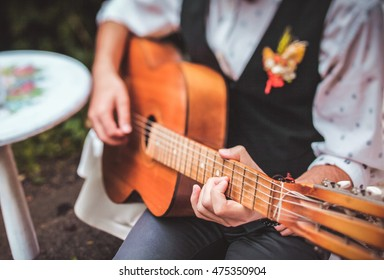 close up finger of guitarist while playing guitar in the outdoor garden