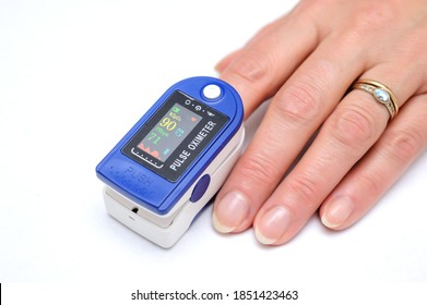 Close up of Finger in an Oximeter Device. Pulse oximeter on white background.