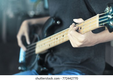 Close up of finger playing chord on electric guitar bass neck.