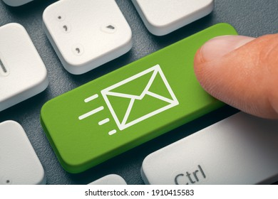 Close up finger pressing computer key with e-mail symbol. Messaging or contacting  on internet. Online communication and networking concept. Envepole symbol on computer key.