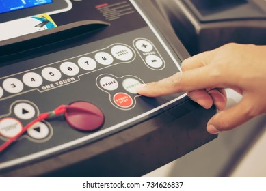 Close up of finger pressing on button of running machine in gym