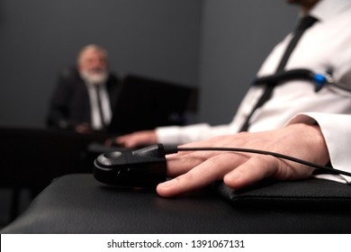 Close up of finger sensor on male finger for measuring pulse. Man siting and holding hands on chair. Polygraph for defining lie or truth. Concept of honesty and security.