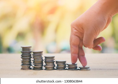 close up finger step on stack of coin, nature copy space background for text, saving and mange money for success business concept, shopping online technology, vintage tone