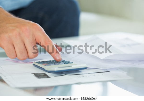 Close up of finger touching calculator in bright living room