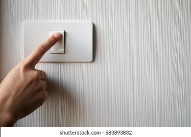 Close up of finger is turning on or off on light switch. Copy space.