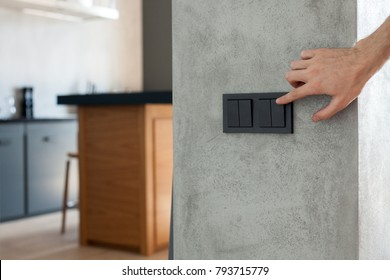 Close up of finger is turning on or off on light switch.