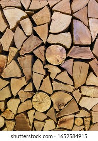 Close up of firewood stacks. Preparation of firewood for winter or wall decorated with dry wooden piles. Vertical mobile photo
