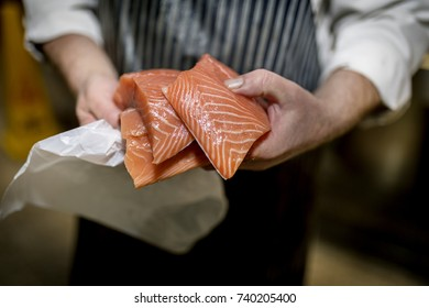 Close up of a fish monger'?s hands holding three fillets of fresh filleted salmon on a market stall in Yorkshire, England