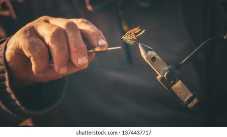 Close up of fisherman tying a fly for fishing