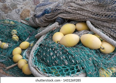 Close up of the  fishing gear and equipment on the port. Various fishing nets,  bobbers, mooring line, floats. Preparing to sail. Fishing at the sea. Drying and repairing nets on the dock.